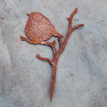 Grand oiseau troglodyte assis sur branche avec pique en fer rouillé