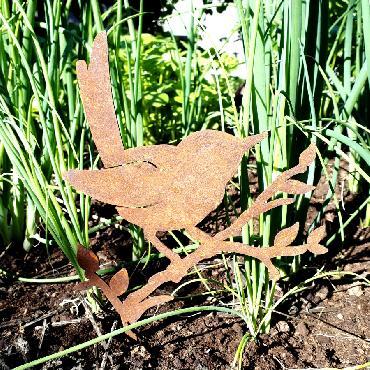 Oiseau merle sur branche feuillue avec pique en fer rouillé