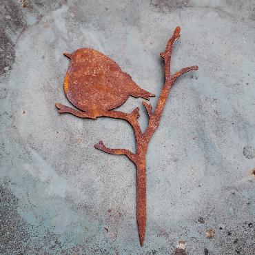 Petit oiseau troglodyte assis sur branche avec pique en fer rouillé